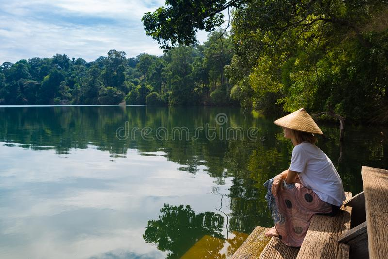 Woman with traditional hat relaxing on water`s edge of volcanic lake surrounded by forest in Banlung, Cambodia, travel destinatio royalty free stock photos