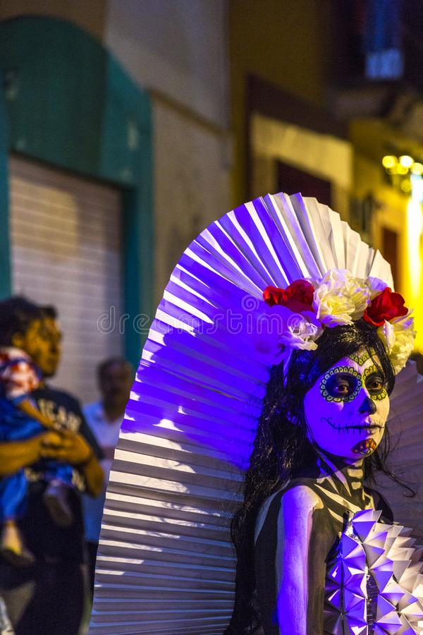 Traditional Day of the Dead Costume. A woman in a traditional Mexican dress carries flowers as part of her costume in Day of the Dead celebrations in Oaxaca stock photography