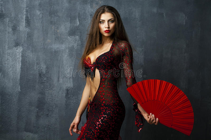 Woman traditional Spanish Flamenco dancer dancing in a red dress. With fan royalty free stock images