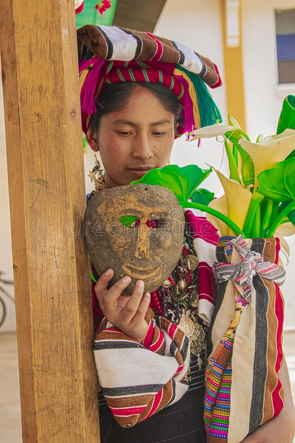 Woman with traditional typical dress and flowers in her hand and wooden mask royalty free stock image