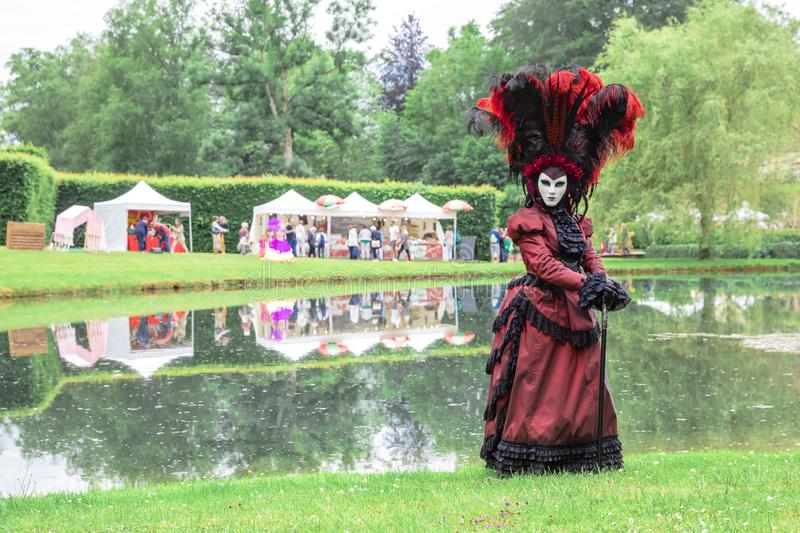 Woman in a traditional Venetian carnival costume and mask against a park background royalty free stock images