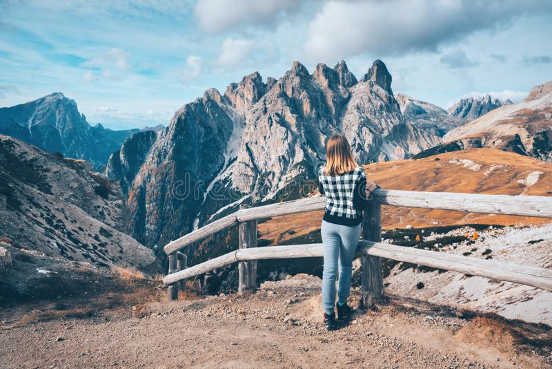 Woman on the trail is looking on majestic mountains at sunset stock photography