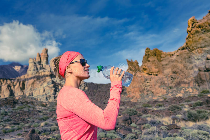 Woman trail runner drinking in inspiring mountains royalty free stock images