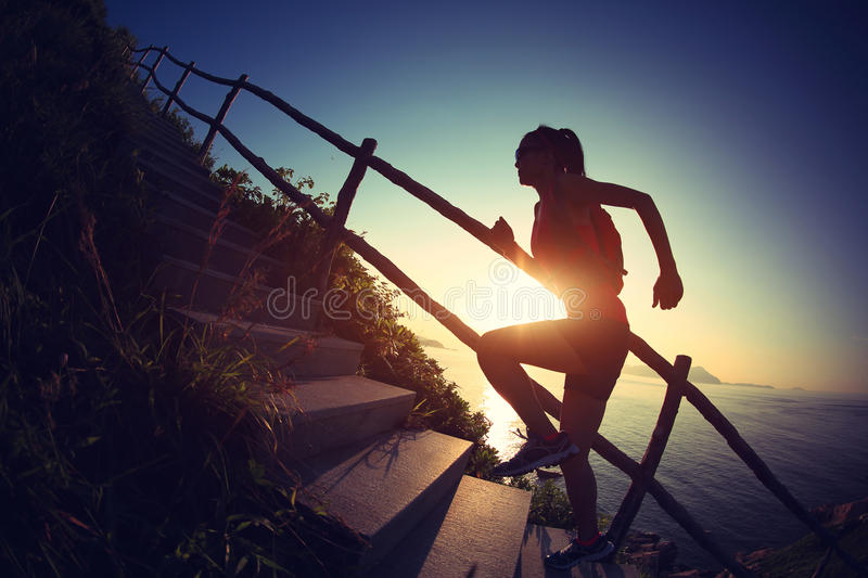 Woman trail runner running up on mountain stairs royalty free stock photography