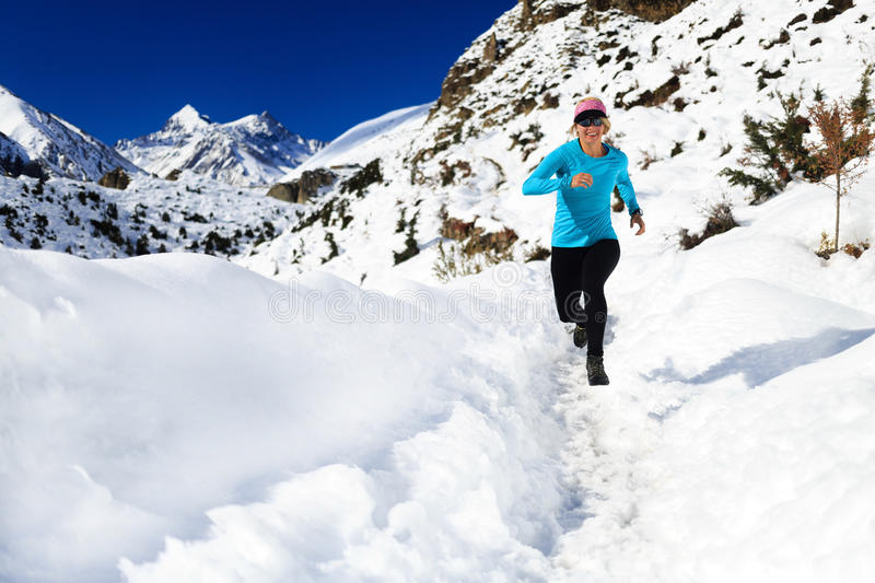 Woman trail running on snow in winter mountains royalty free stock photo