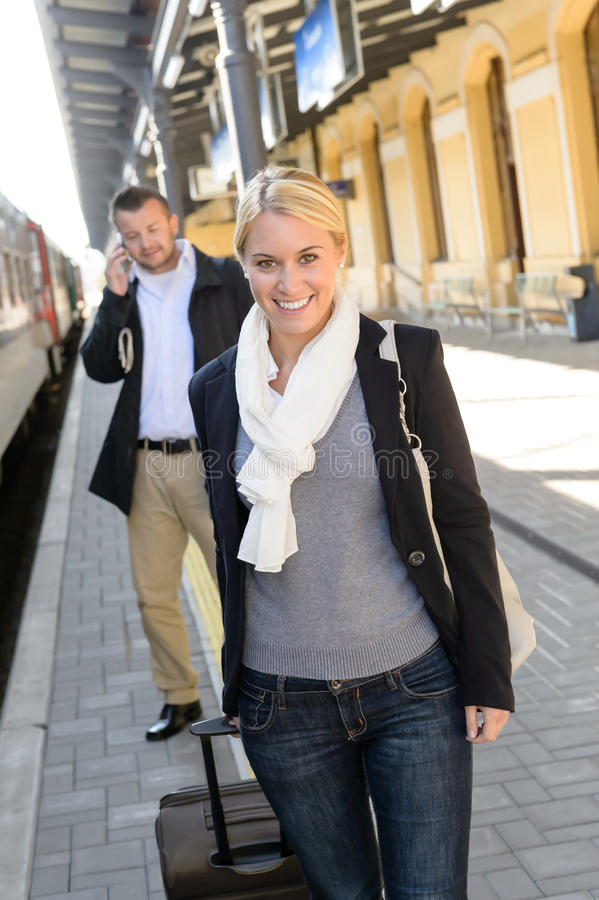 Woman in train station man on cellphone royalty free stock photography