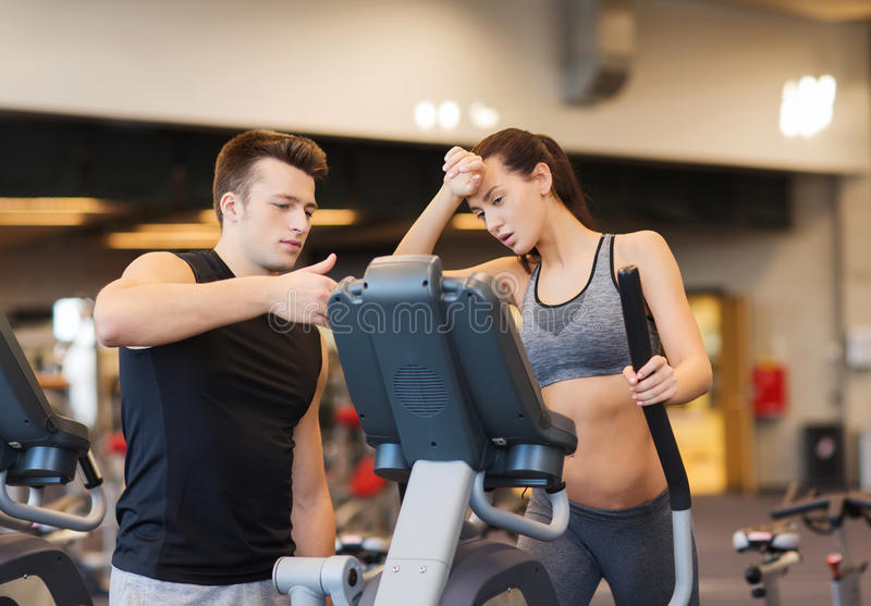 Woman with trainer exercising on stepper in gym. Sport, fitness, lifestyle, technology and people concept - tired women with trainer exercising on stepper in gym stock image