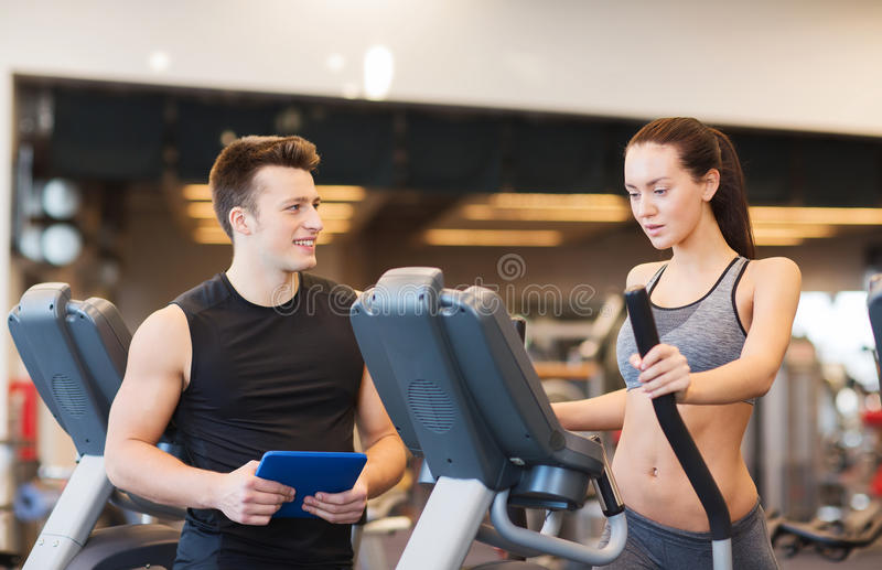 Woman with trainer exercising on stepper in gym. Sport, fitness, lifestyle, technology and people concept - women with trainer exercising on stepper in gym stock images