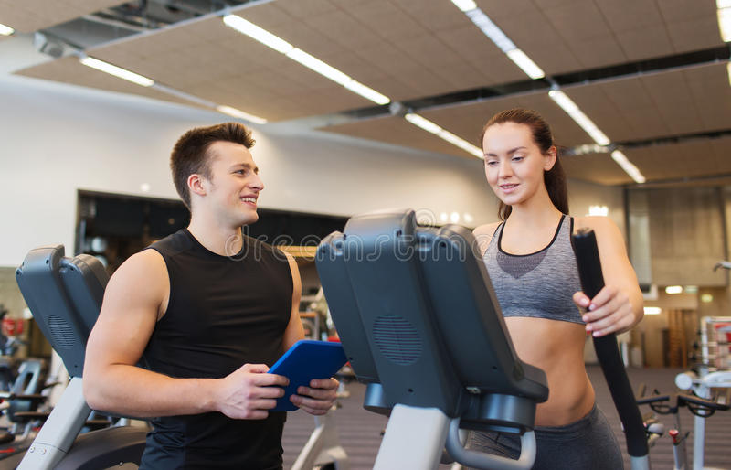 Woman with trainer exercising on stepper in gym. Sport, fitness, lifestyle, technology and people concept - women with trainer exercising on stepper in gym royalty free stock image
