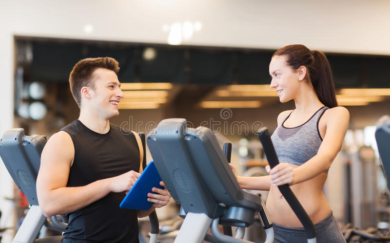 Woman with trainer exercising on stepper in gym. Sport, fitness, lifestyle, technology and people concept - women with trainer exercising on stepper in gym stock photos