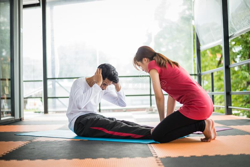 Woman trainer help sportsman sit ups in gym. Woman trainer help sportsman sit ups on the floor in gym royalty free stock photos