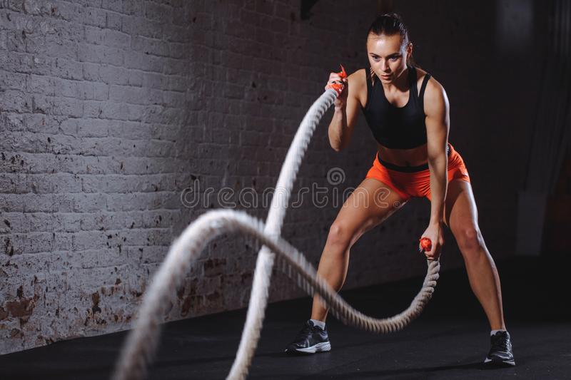 Battle ropes session. Attractive young fit and toned sportswoman training in gym. Woman training with battle rope in cross fit gym stock image