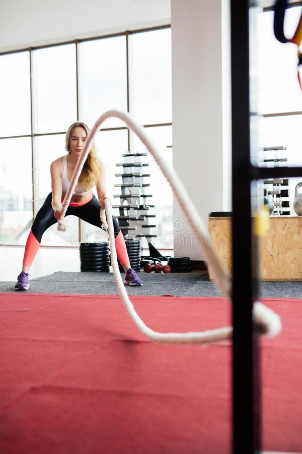 Young Woman training with battle rope in cross fit gym stock photos