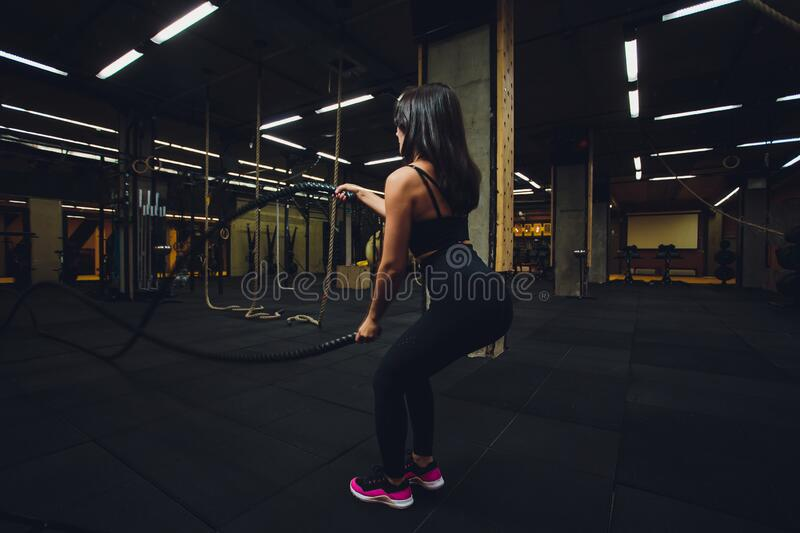 Woman training with battle ropes in gym, doing intense hard training. Woman training with battle ropes in gym, doing intense hard training royalty free stock photography