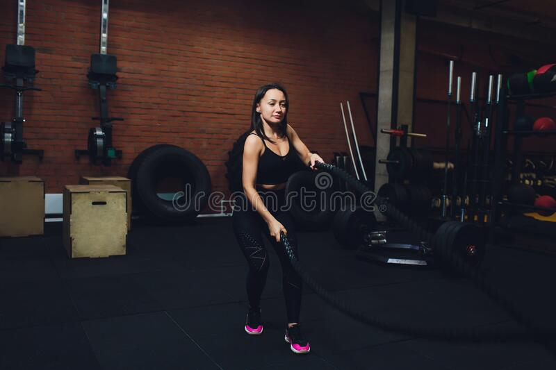 Woman training with battle ropes in gym, doing intense hard training. Woman training with battle ropes in gym, doing intense hard training stock photo