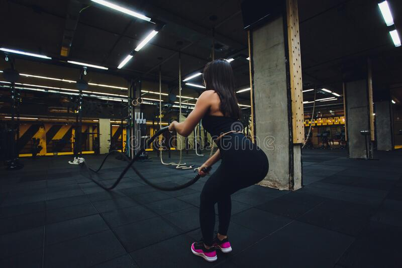 Woman training with battle ropes in gym, doing intense hard training. Woman training with battle ropes in gym, doing intense hard training royalty free stock images