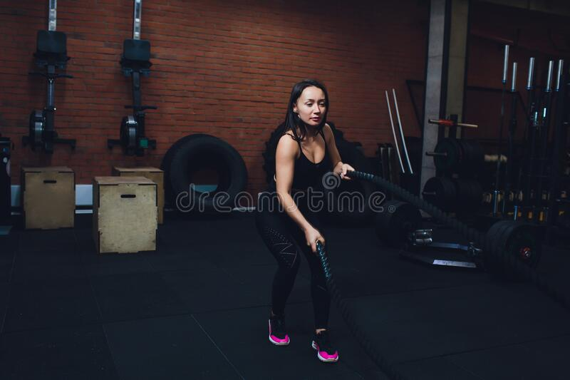 Woman training with battle ropes in gym, doing intense hard training. Woman training with battle ropes in gym, doing intense hard training royalty free stock image