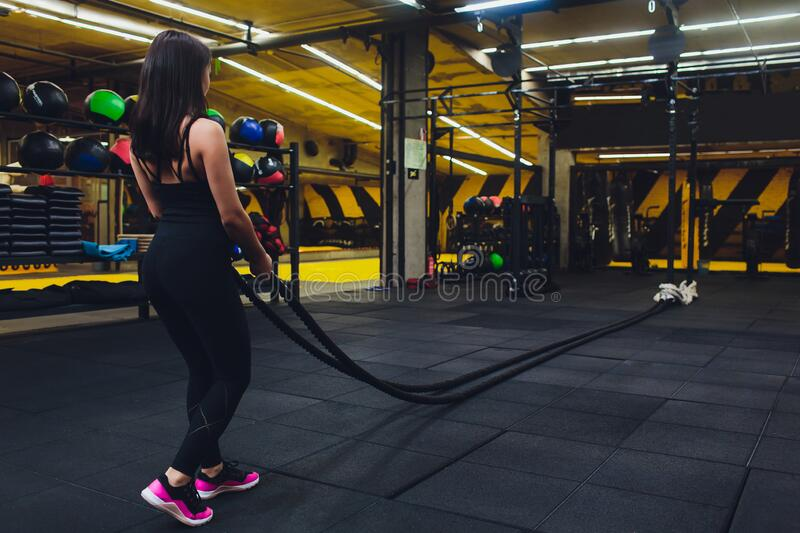 Woman training with battle ropes in gym, doing intense hard training. Woman training with battle ropes in gym, doing intense hard training stock photos
