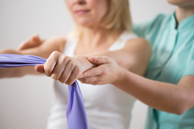 Woman training with exercise band. Assisted by physiotherapist stock photo