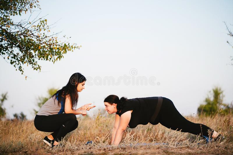 Woman training with fitness instructor support. Street workout, motivation, sport, outdoor activity, healthy lifestyle concept. Personal trainer giving royalty free stock image