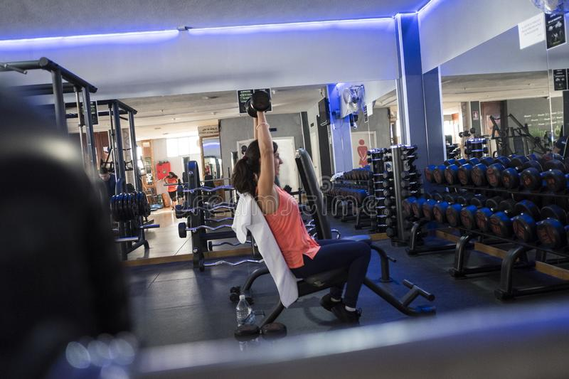 Woman training in gym with weights royalty free stock photos