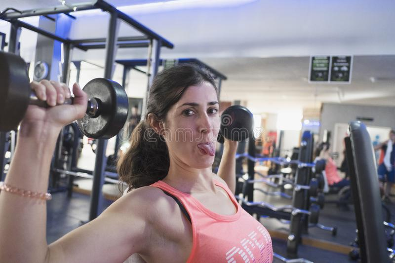 Woman training in gym with weights royalty free stock images