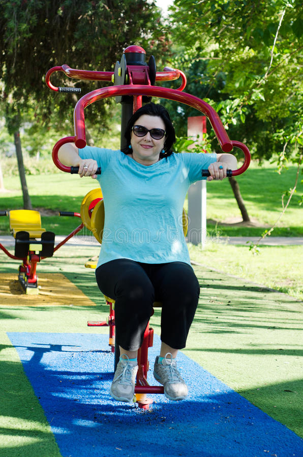 Woman training on a Lat Pull fitness machine outdoor. Mature woman training on a Lat Pull machine at outdoor fitness circuit in the green sunny park stock image