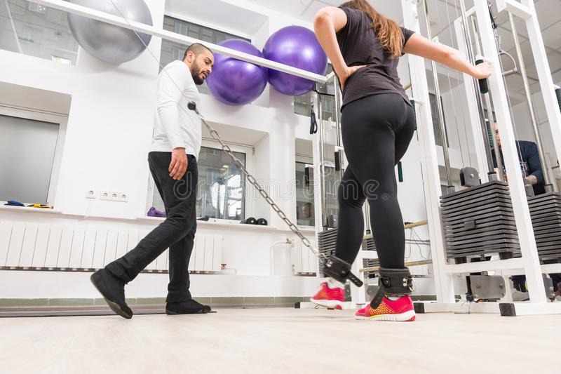 Woman training legs during workout at gym. Woman training legs on cable machine during workout at gym with personal trainer stock photography