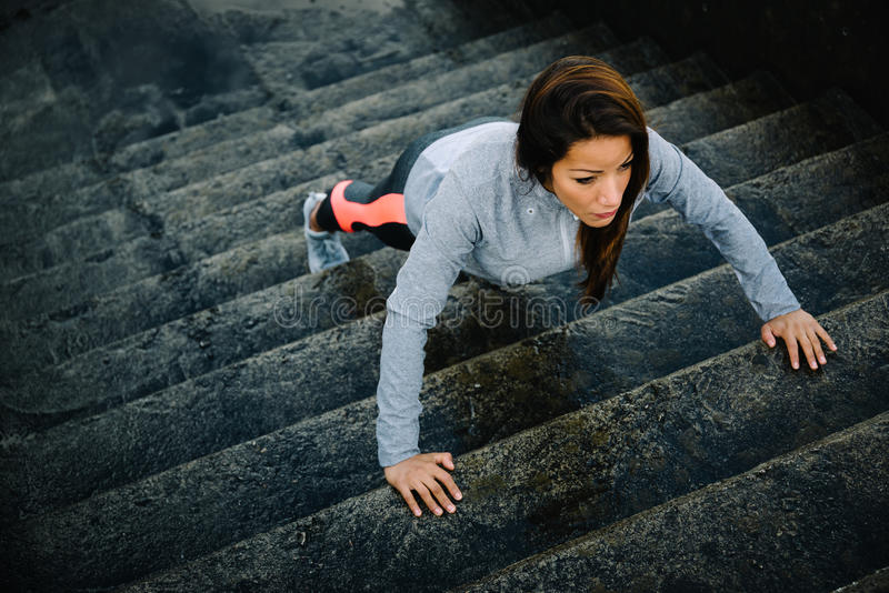 Woman training stairs push ups on urban workout stock images
