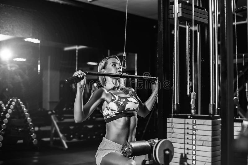 Woman training with weight-lifting training machine. Young blonde Woman training back with weight-lifting training machine royalty free stock photos