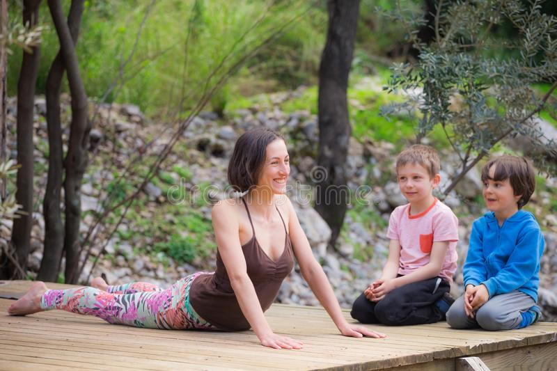 A woman trains with children in the yard royalty free stock photo