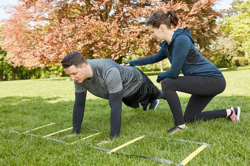Woman trains man as Personal Trainer royalty free stock image