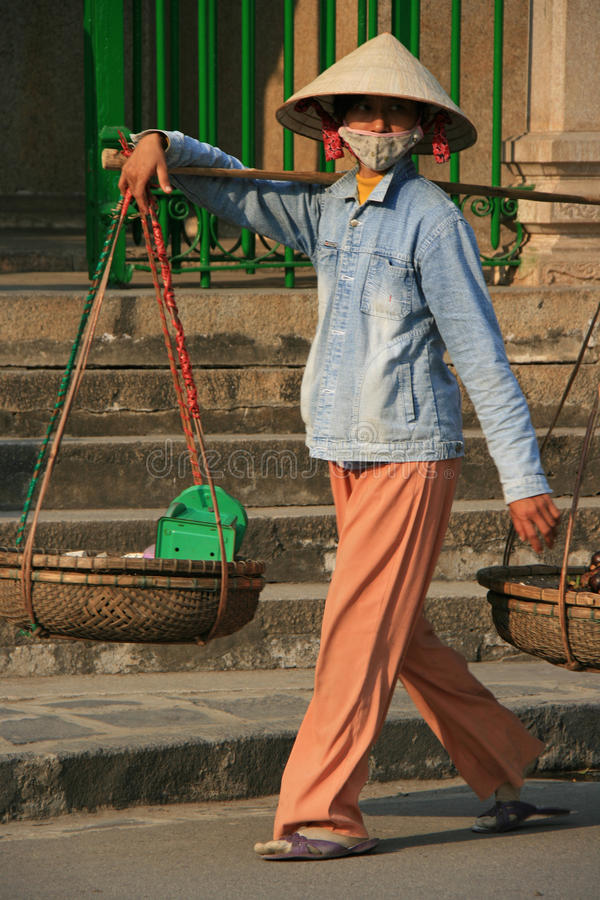 A woman is transporting goods in baskets in Hoi An (Vietnam) stock photography