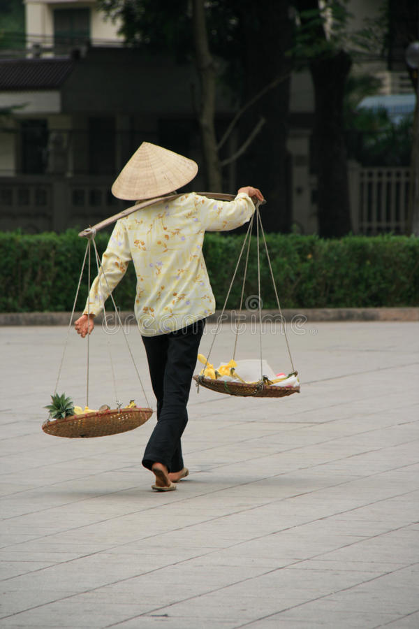 A woman is transporting goods in baskets in a street of Hanoi (Vietnam) stock photography