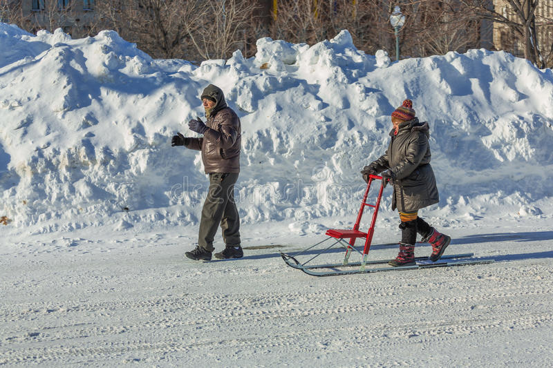 A woman transports her sled stock image