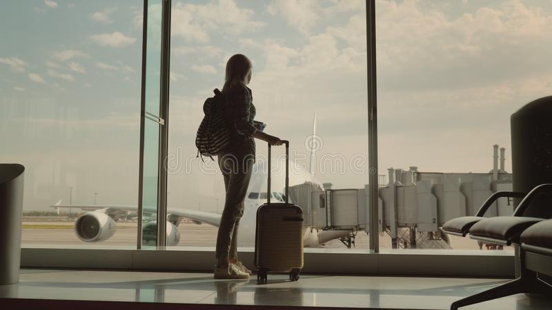 A woman with a travel bag and boarding passes in her hand looks at a huge airliner behind the airport terminal royalty free stock images