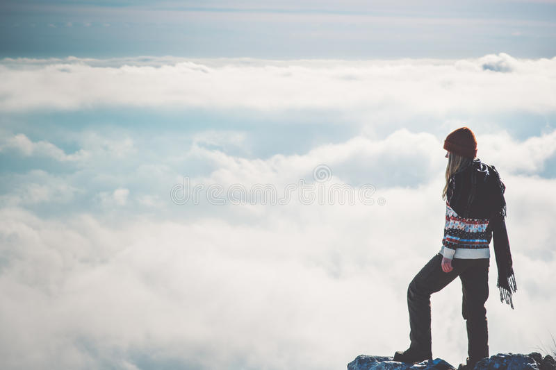 Woman Traveler alone on cliff over clouds stock image