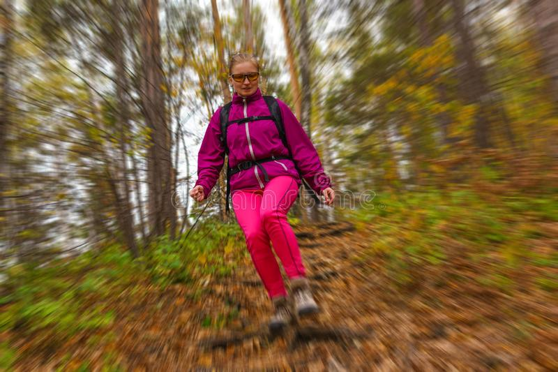Woman traveler descends from a hill in the autumn forest, radial blur background. Woman traveler with a backpack goes down the hill along the trail in the autumn stock photo