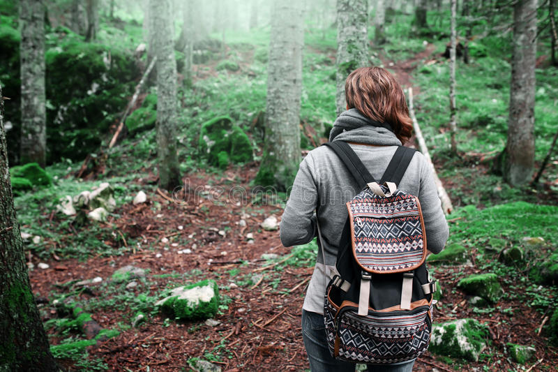 Woman traveler with backpack in green forest stock photo