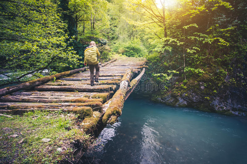 Woman Traveler with backpack hiking on bridge over river stock photos
