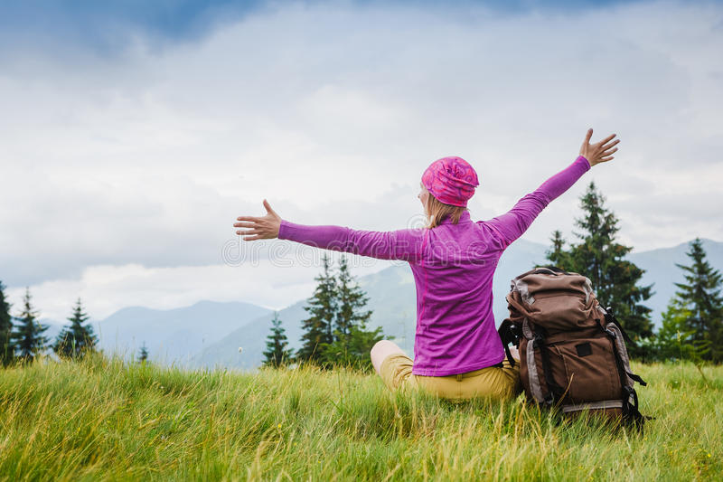 Woman Traveler with Backpack hiking in the Mountains. With beautiful summer landscape royalty free stock photos