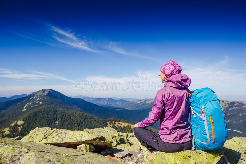 Woman Traveler with Backpack hiking in the Mountains and beautiful summer landscape royalty free stock photo