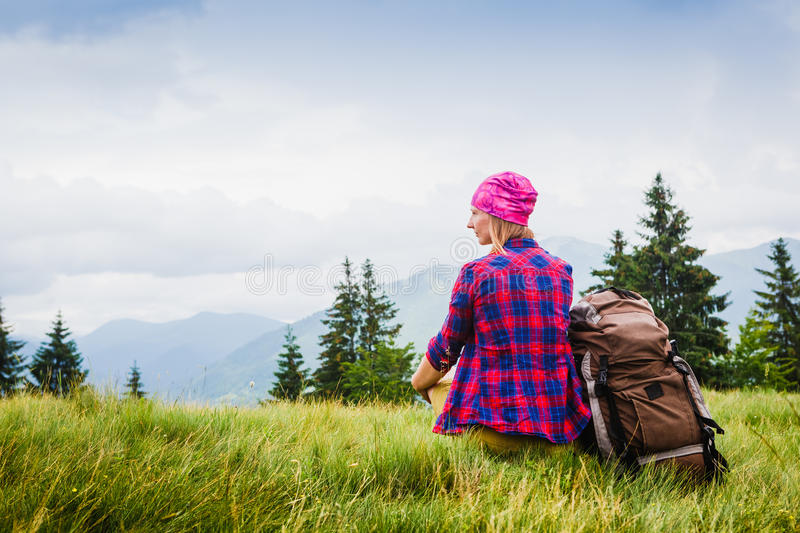 Woman Traveler with Backpack hiking in the Mountains with beautiful summer landscape stock photos