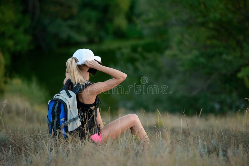 Woman traveler with backpack holding cap and looking at amazing stock photos