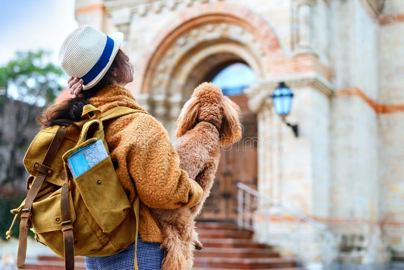 Woman traveler with backpack holding dog examines architectural monument . Concept of travel royalty free stock photos