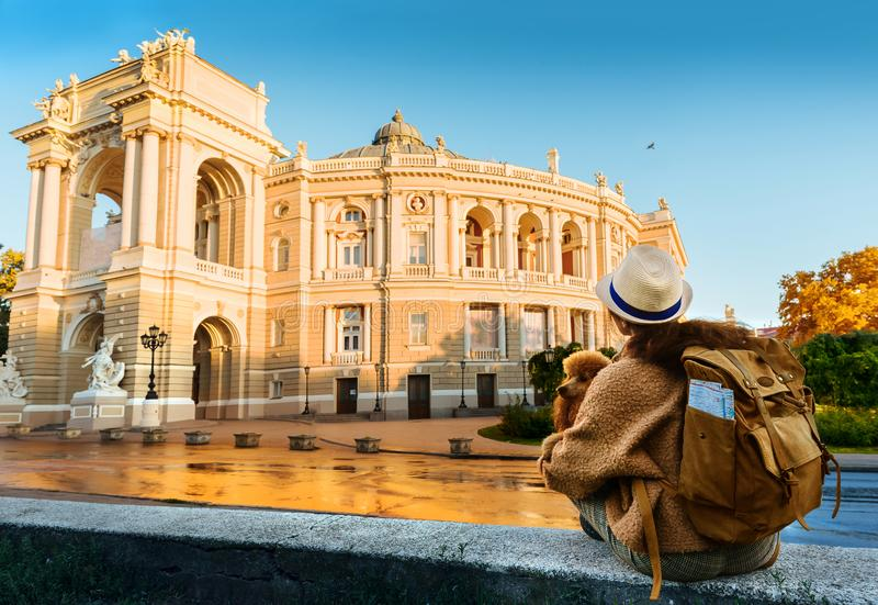 Woman traveler with backpack holding dog examines architectural monument . Odessa Opera Theatre royalty free stock photography