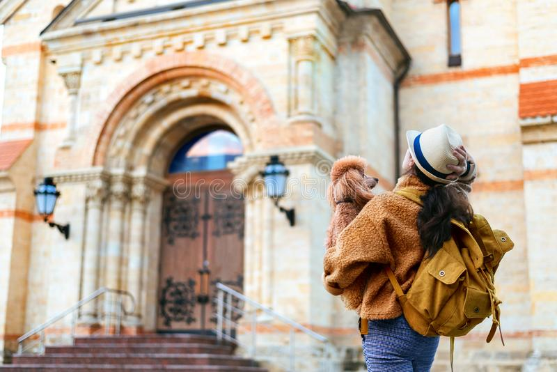 Woman traveler with backpack holding dog examines architectural monument . Concept of travel royalty free stock images