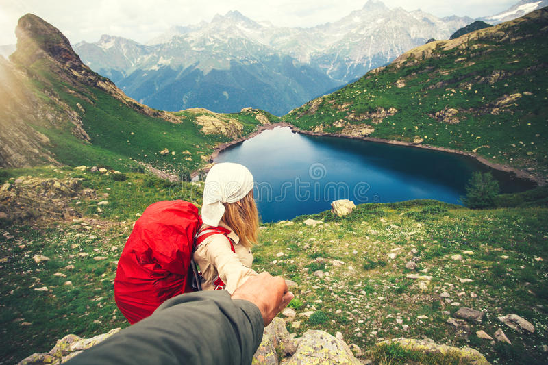 Woman Traveler with backpack holding Man hand following Travel hiking stock image
