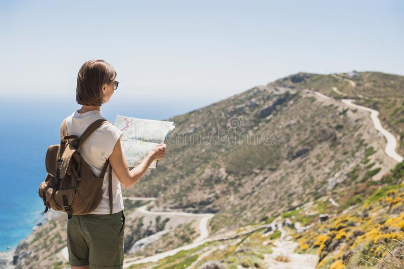 Woman traveler with backpack holding map. Travel, tourism, summer holidays, active lifestyle concept. Hipster tourist girl looking stock photos