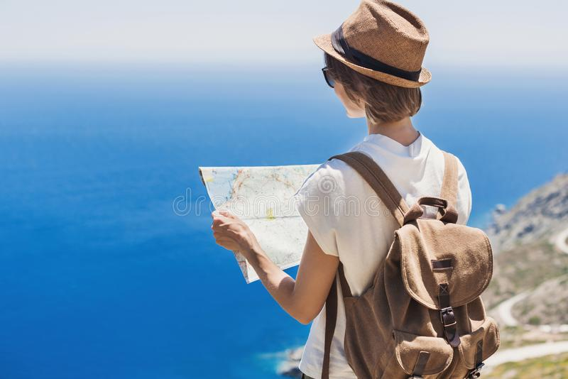 Woman traveler with backpack holding map. Travel, tourism, summer holidays, active lifestyle concept. Hipster tourist girl looking royalty free stock photo